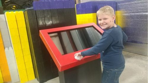 Boy smiling at camera standing in front of a Giant Etch A Sketch